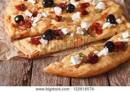 Sliced Italian Focaccia With Tomatoes, Feta And Olives Closeup Horizontal