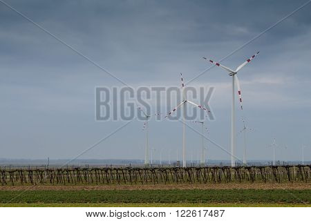 Wind turbine and an early spring field in Berg Austria. Rainy cloudy sky.
