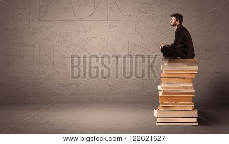 A serious businessman in suit sitting on a pile of giant books in front of a greyish brown wall with drawn lines, angles, numbers, circles and curves.