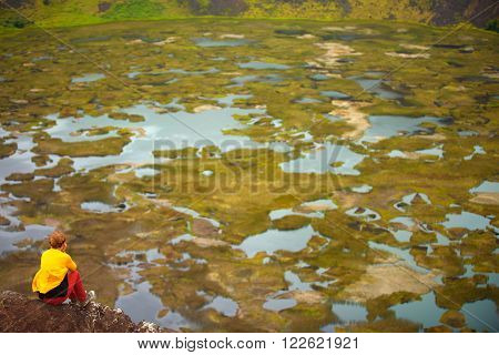 girl sitting on the edge of the Rano Kau volcano Easter island Chile South America