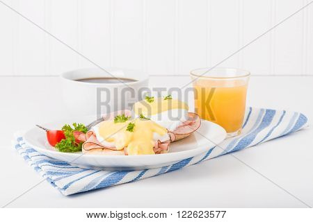 Delicious eggs benedict served with fresh coffee and orange juice.