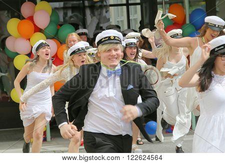 STOCKHOLM SWEDEN - JUN 10 2015: Group of happy teenagers wearing graduation caps running out from school after graduation from high school at the school Globala gymnasiet June 10 2015 Stockholm Sweden