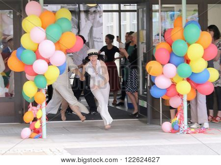 STOCKHOLM SWEDEN - JUN 10 2015: Happy teenage girls running out from school after graduation from high school at the school Globala gymnasiet June 10 2015 Stockholm Sweden