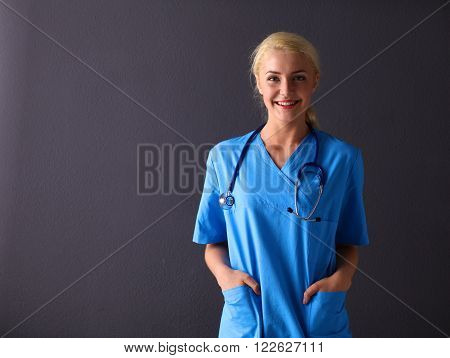 Young doctor woman with stethoscope isolated on gray background.