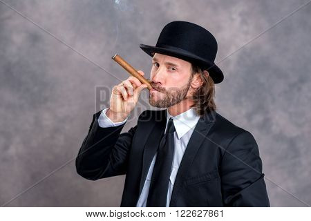 Businessman With Bowler Hat In Black Suit Smoking Big Cigar