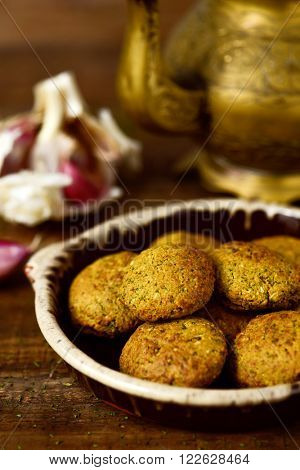 closeup of an earthenware plate with some falafel on a rustic wooden table with a golden teapot in the background