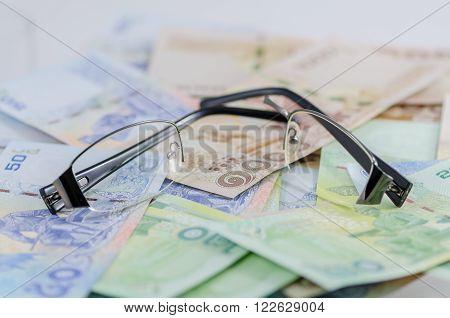 Broken black glasses on Thai baht money ** Note: Shallow depth of field