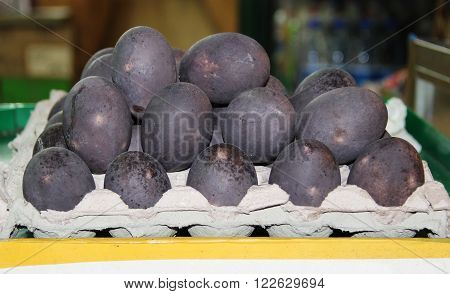 Chicken eggs with dark shells in the carton box. China.