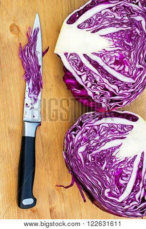 in the photo shows the two halves of red cabbage and a kitchen knife