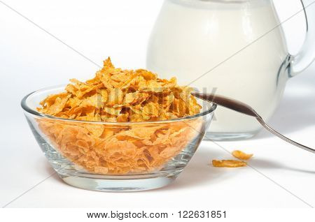 Healthy breakfast cornflaGlass bowl with sugar-coated corn flakes on white tablekes with milk