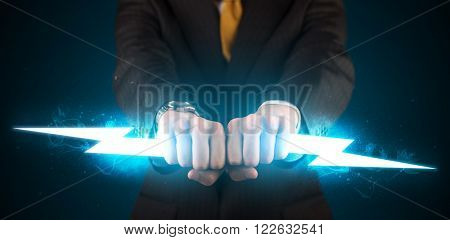 Business man holding glowing lightning bolt in his hands concept