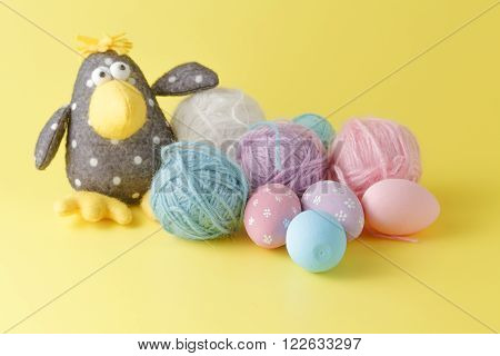 Toy crow on yellow background with wool clew and easter eggs