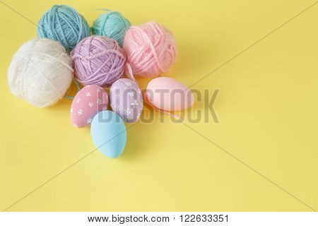 Pastel and colored Easter eggs and wool clew