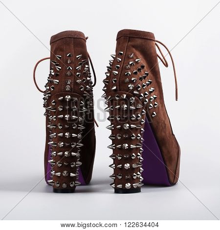 Pair of brown high heel shoes with spikes isolated on white background