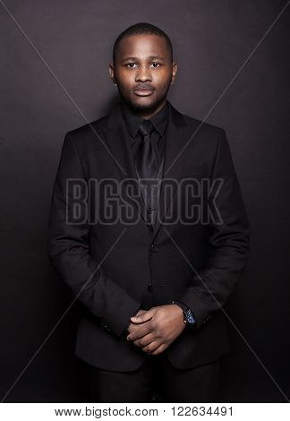 Close up portrait of a handsome young African American businessman in suit smiling in studio with black background