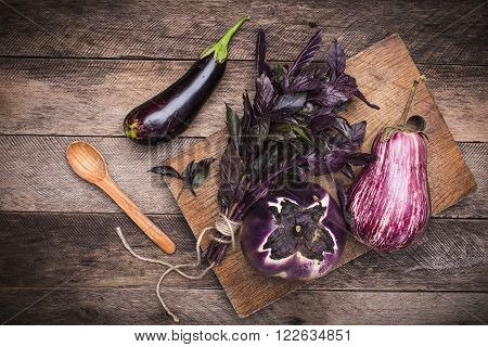Aubergines, Basil And Spoon On Chopping Board And Wooden Table