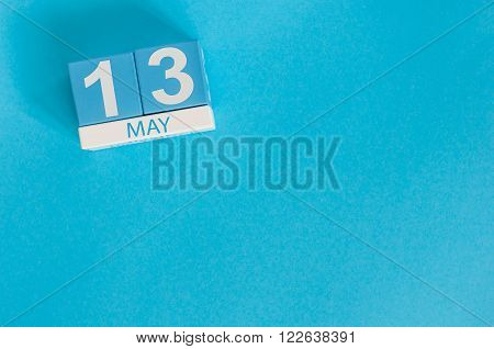 May 13th. Image of may 13 wooden color calendar on blue background.  Spring day, empty space for text.