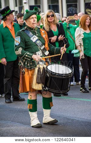 New York NY USA - March 17 2016: A drummer dressed in a kilt marches in the St Patrick's Day Parade on on 5th Ave in New York City.