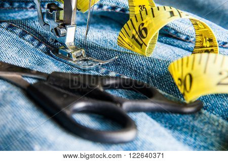 Production of garment with a sewing machine -  jeans, centimeter, scissors