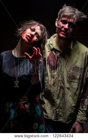 KIEV,UKRAINE - February 20 : Guy and girl in dirty clothes with blood on his face looking at the camera during the quest game in zombie theme in Kiev,Ukraine on February 20,2016.