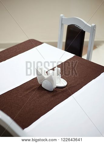 Generic view of restaurant table with table covered by tablecloth anf napkins on it empty table close up