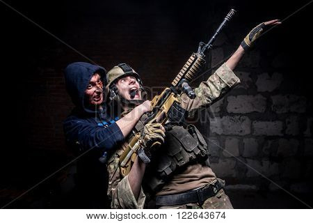 KIEV,UKRAINE - February 20 :  Actor dressed as a zombie attacks soldier with gun during the quest game in zombie theme in Kiev,Ukraine on February 20,2016.