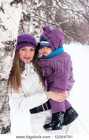 Mother  Keeps A Small Child In Her Arms. A Walk In The Snowy Winter Park.
