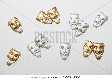 Small Greek drama masks in gold and silver on white backgroun