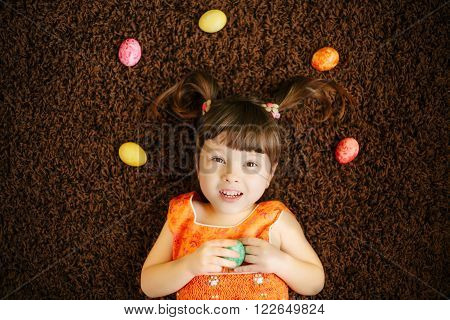 cheerful little girls with eggs. easter eggs. top view. flat lay. happy kid. little child. orange dress