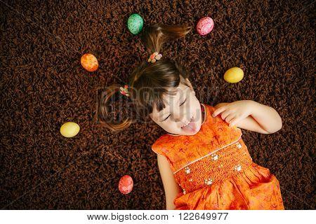 little girls with eggs showing tongue. easter eggs. top view. flat lay. happy kid. little child. orange dress