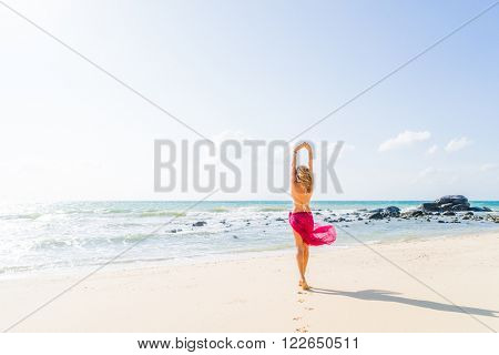 Portrait of young woman wearing a pink sarong and bikini on the tropical beach
