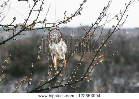 Handmade native american dream catcher on background of rocks and lake. Tribal elements feathers