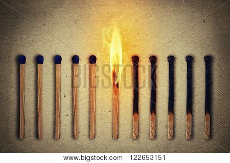 Burning match standing middle a row of whole new matches at left and extinguished at right. Leadership concept