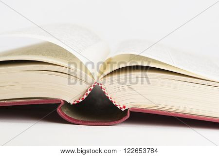 An open red hardcovered book on white background