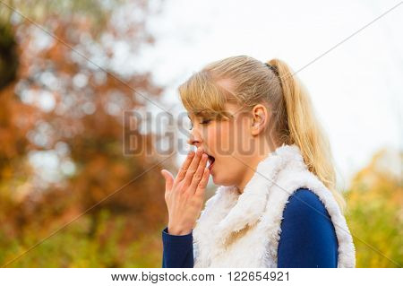 Seasons happiness and outdoors activities. Spending time outdoors on fresh air. Young girl walk outside in autumnal park. Take break from chores and work tired yawning.