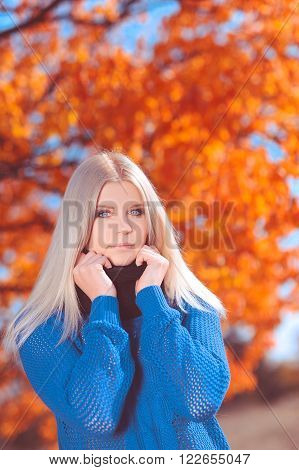 Beautiful girl 20-24 year old wearing blue sweater at autumn background outdoors. Looking at camera. Young adults.