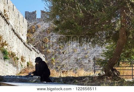 Greece, Rhodes - July 12 A woman begs near the fortified walls of the Old Town on July 12, 2014 in Rhodes, Greece