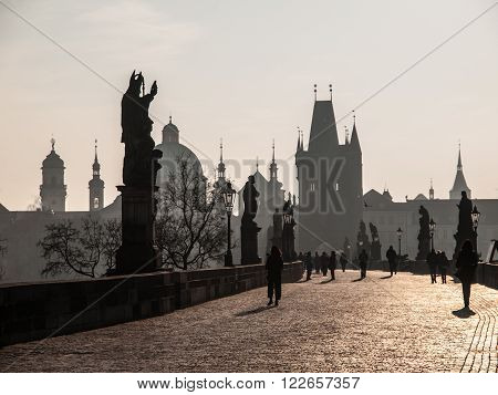 Tourists walk on Charles Bridge on sunny morning under silhouettes of statues and Old Town towers, Prague, Czech Republic