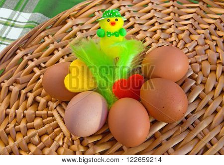 Eggs with easter decoration (cute neatly hatted chicken with bow tie) and two felt hearts on wicker tray.