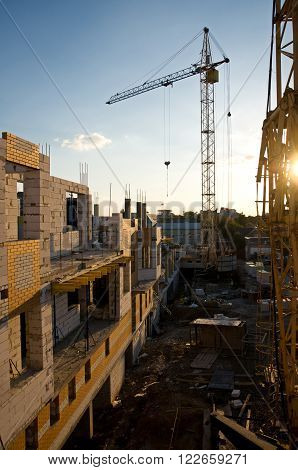 Buildings under construction and tall crane at evening