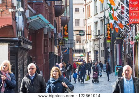 LIVERPOOL, UNITED KINGDOM - MARCH 20th 2016 - Tourists walk down Mathew Street in Liverpool passing the entrance to the Cavern Club at 10 Mathew Street, The Cavern Quarter, Liverpool, Merseyside, England, UK.