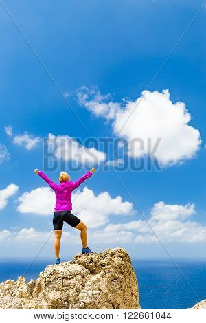 Success achievement running or hiking accomplishment or business concept woman celebrating with arms up raised outstretched trekking climbing trail running outdoors. Motivation and inspiration looking at beautiful landscape view.