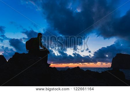 Hiker or runner silhouette backpacker man looking at inspirational ocean landscape and islands on mountain peak. Accomplished man admire beautiful night and sea. Adventure and lifestyle concept.