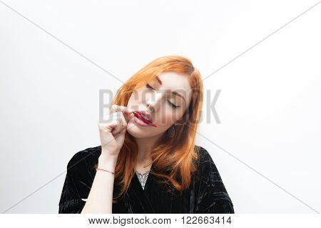 Young redhead woman portrait with close eyes tasting a red hot chili pepper between lips