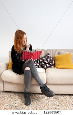Young Woman Reading A Book On A Sofa