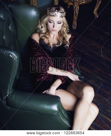 young blond woman wearing crown in fairy luxury interior with empty antique frames total wealth, rich lifestyle concept