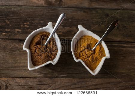 curcuma and curry spices on wooden table with the spoons ready to serve