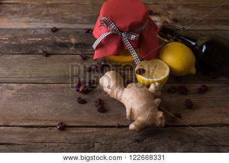 jar with honey and ginger and bottle of white with lemon and ginger on wood