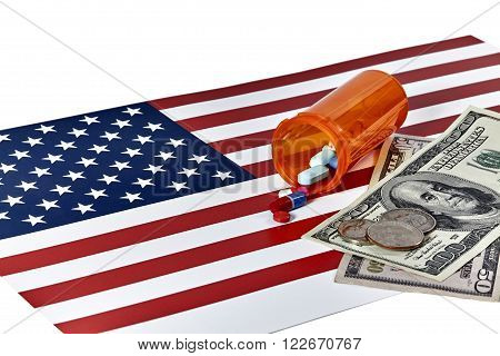 Prescription Medications laying on an American Flag with US Currency and Coins isolated on white