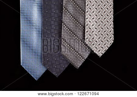 four neckties hanging vertically and isolated against black background
